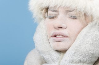Frozen. Close-up portrait of chilled female face covered in snow ice.