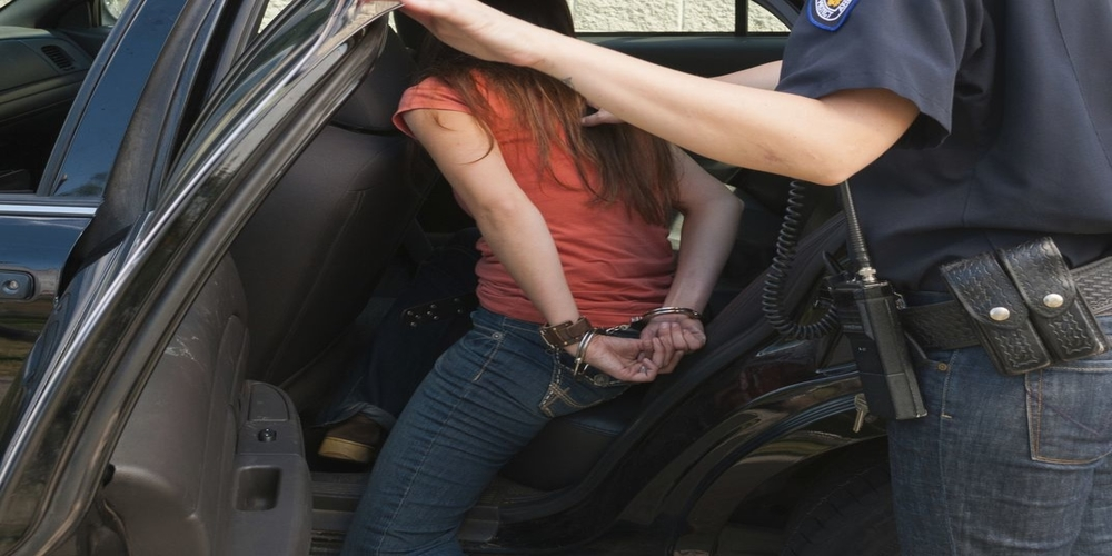 Female police officer putting handcuffed woman in car
