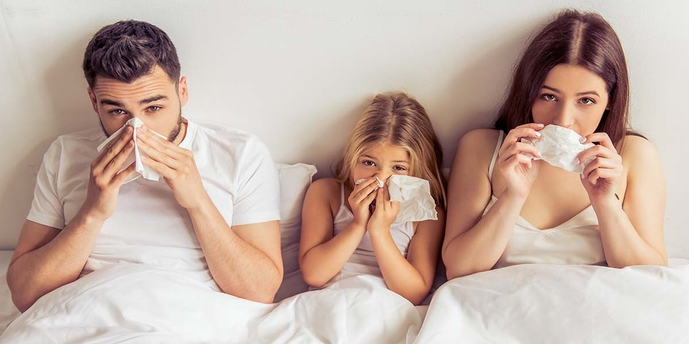 Beautiful young parents and their daughter are having common cold, wiping noses and looking at camera while lying on bed